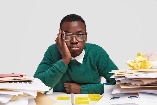 Znudzony pracownik ma zmęczony wyraz twarzy, wygląda niezadowolony, pracuje wiele godzin nad zadaniem projektowym, ma ciemną, zdrową skórę, wkłada notatki do notatnika
