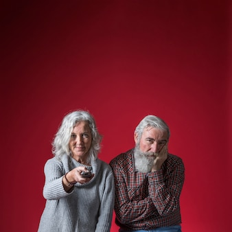 Znudzony starszy mężczyzna oglądanie telewizji z żoną na czerwonym tle