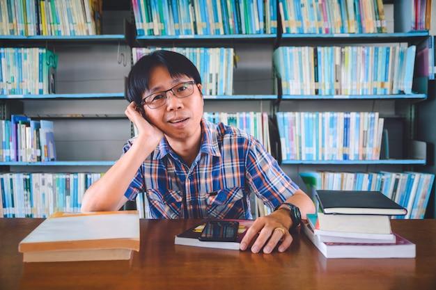 Znudzony student azjatyckich z książkami w bibliotece