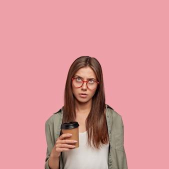 Znudzony student pozuje na różowej ścianie
