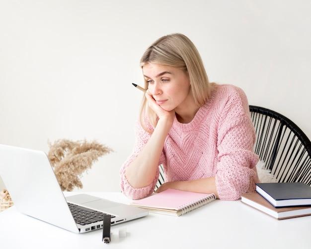 Znudzony student słucha koncepcji e-learningowych kursów