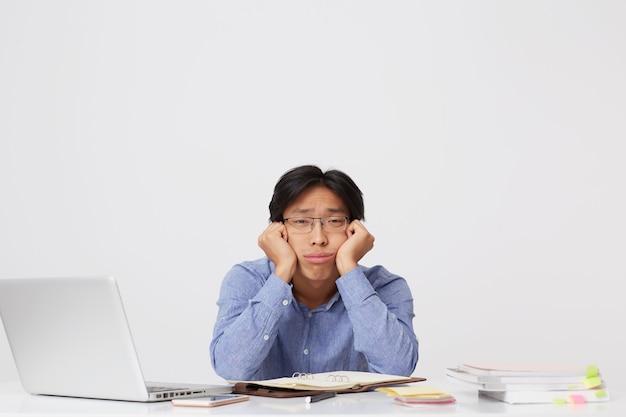 Znudzony, zestresowany azjatycki młody biznesmen w okularach z głową na rękach siedzi w miejscu pracy przy stole i czuje się zmęczony na białym tle nad białą ścianą