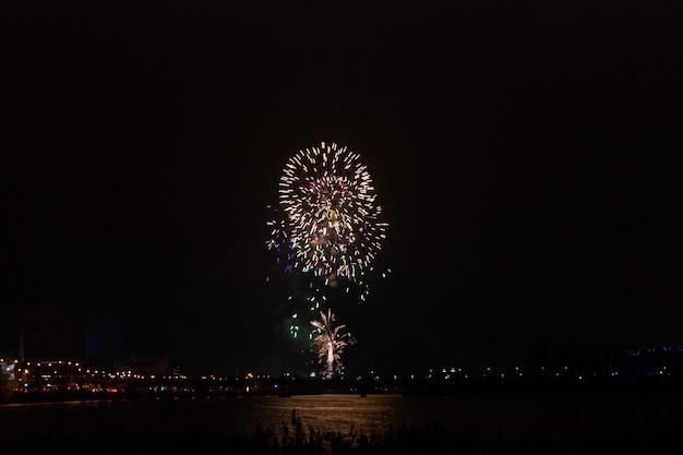 Zobacz fajerwerki na tle ciemnej nocy nad miastem. koncepcja wakacje i zabawa