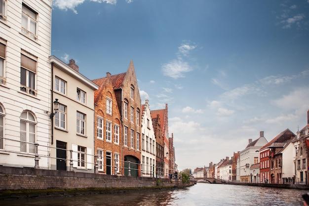 Zobacz kanał i kolorowe tradycyjne domy na tle zachmurzonego nieba w popularnym belgijskim mieście brugge, belguim