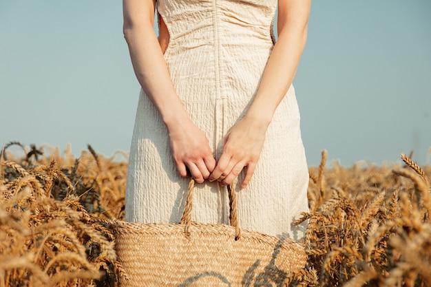 Zobacz na białej kobiecie w sukience trzymającej torbę na polu pszenicy