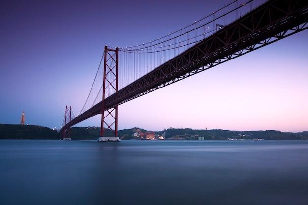 Zobacz o zmierzchu 25 kwietnia bridge w lizbonie, portugalia. miejsce na tekst.