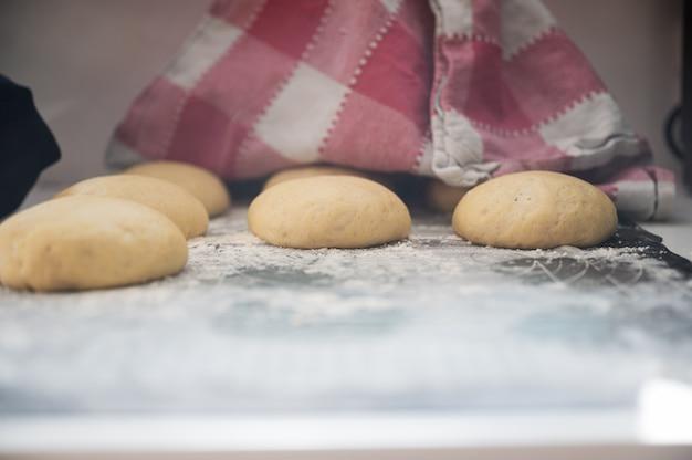 Zobacz pod bawełnianą ściereczką kuchenną rosnące domowe bułki lub pączki