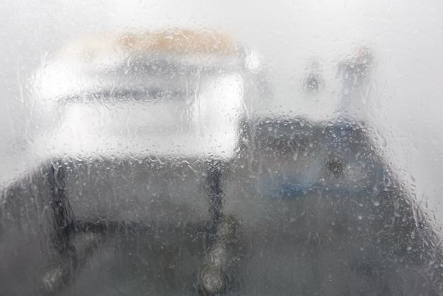Zobacz przez mokre szkło na suszeniu części samochodu w kabinie lakierniczej