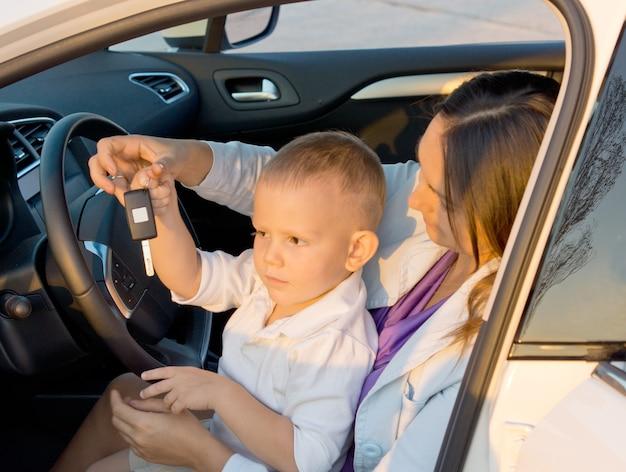 Zobacz przez otwarte drzwi samochodu małego chłopca siedzącego na kolanach matki, bawiącego się kluczykiem samochodowym