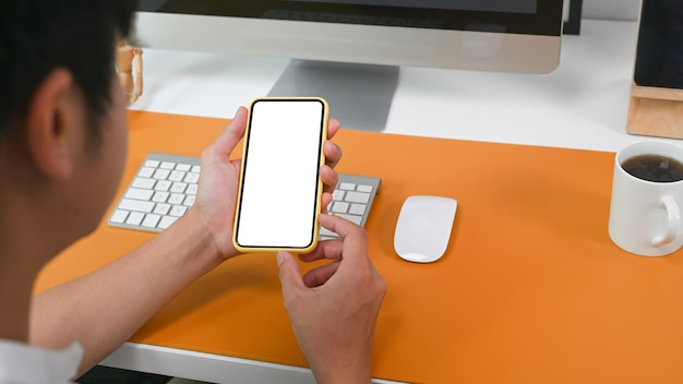 Zobacz przez ramię biznesmena siedzącego przy biurku i przy użyciu telefonu komórkowego.