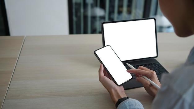 Zobacz przez ramię bizneswoman przy użyciu telefonu komórkowego i pracy z tabletem komputerowym.
