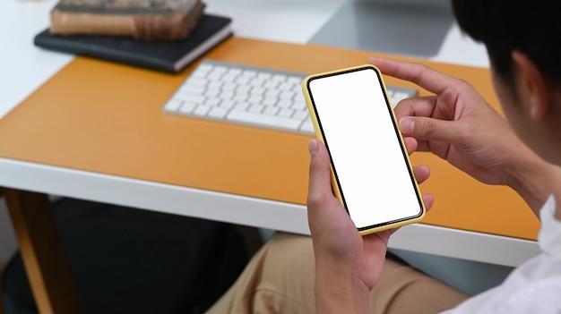 Zobacz przez ramię dorywczo biznesmen za pomocą inteligentnego telefonu w biurze.