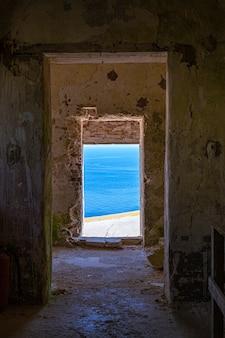 Zobacz przez stary opuszczony, zniszczony budynek na niebieskim krajobrazie. morze adriatyckie. apulia, włochy.