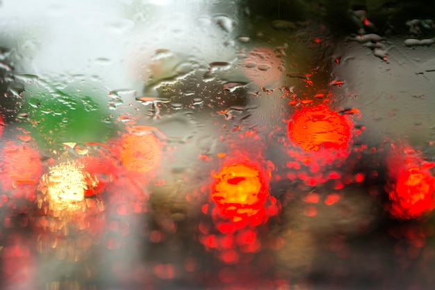Zobacz przez szybę samochodu na światłach samochodów w deszczu. rozmycie na mokrym szkle.