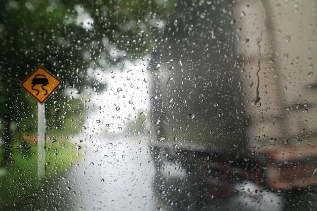 Zobacz przez wiatrową tarczę deszczowego dnia ze znakiem drogowym, płytka głębia ostrości kompozycji.