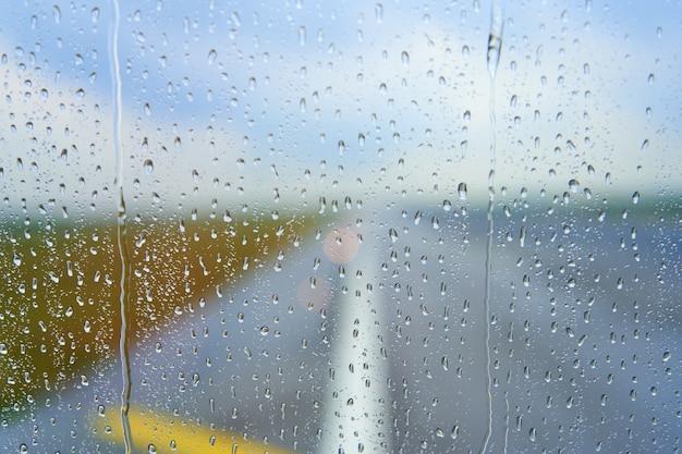 Zobacz przez zamgloną szybę samolotu przed startem w deszczowy dzień