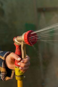 Zobacz ręce kobiety podlewania roślin z węża, sprawia, że deszcz w ogrodzie. ogrodnik z wężem do podlewania i opryskiwaczem wody na kwiaty.