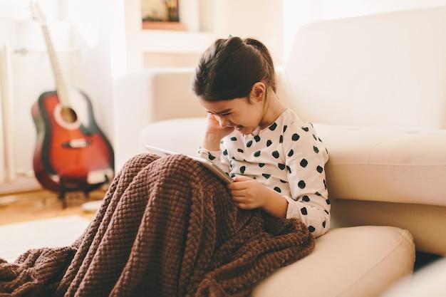 Zobacz w pięknej małej dziewczynki siedzi na podłodze trzymając tabletkę