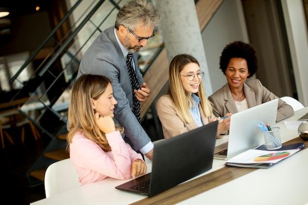 Zobacz wieloetniczną grupę ludzi biznesu pracujących razem i przygotowujących nowy projekt na spotkanie w biurze