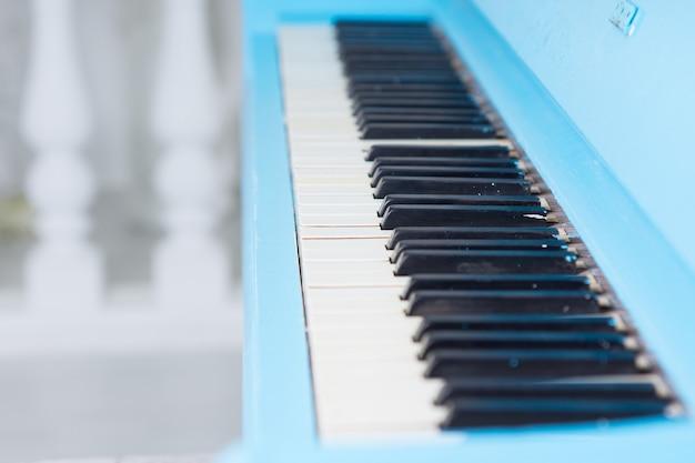 Zobacz wzdłuż niebieskiej klawiatury fortepianowej z otwartą pokrywą, aby wyświetlić kość słoniową klawiszy koncepcyjnych rozrywki i klasycznego wykonania