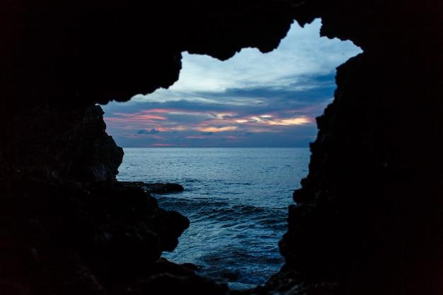 Zobacz z jaskini balinesse na plaży oceanu na ciemnym niebieskim niebie