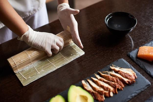 Zobacz zbliżenie procesu przygotowania toczenia sushi. ręce mistrza wykonujące rolkę sushi z matą bambusową.