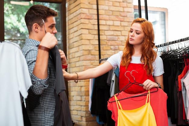 Zobaczmy. spokojna, zamyślona dziewczyna przygląda się uważnie swojemu chłopakowi trzymającemu modną koszulkę w sklepie z ubraniami