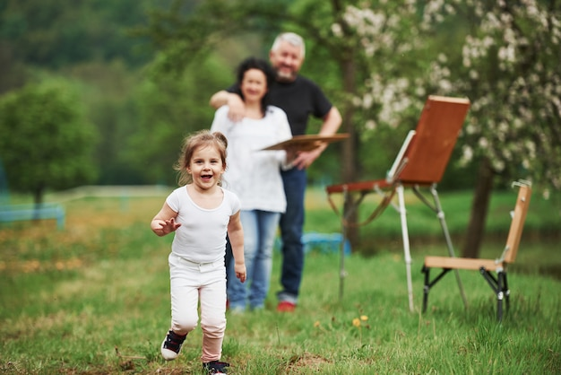 Zogniskowane zdjęcie. babcia i dziadek bawią się na świeżym powietrzu z wnuczką. koncepcja malarstwa