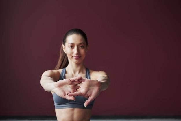 Zogniskowane zdjęcie. dziewczyna z dobrą sylwetką fitness ma ćwiczenia w przestronnym pokoju