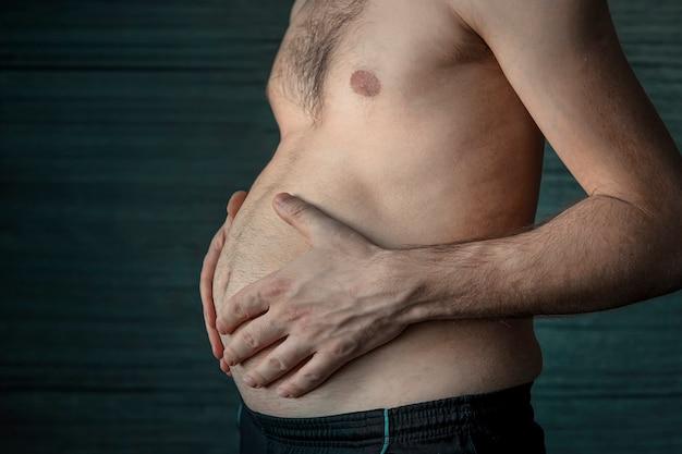 Żołądek mężczyzny z bliska. koncepcja - nadwaga. dorosły mężczyzna trzyma w dłoniach swój wielki brzuch. problem otyłości u młodych mężczyzn.