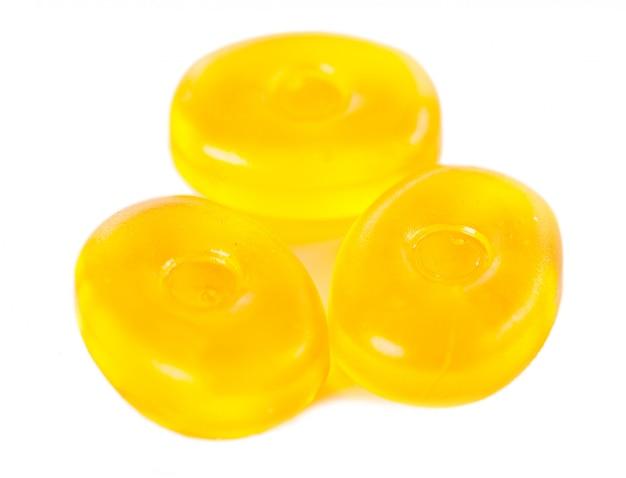 Żółci cukierki odizolowywający na bielu