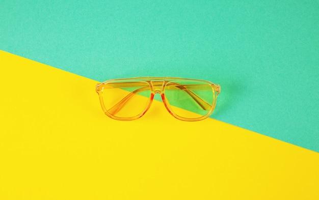 Żółci fahionable okulary przeciwsłoneczni na abstrakcjonistycznym koloru papieru tle