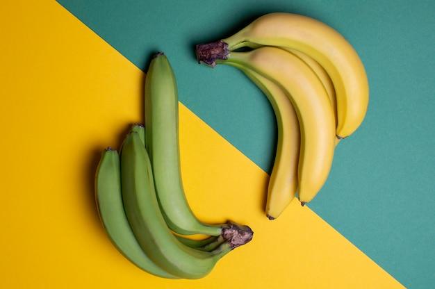 Żółci i zieleni banany na barwionym stole, dojrzałym i niedojrzałym owocowym pojęciu