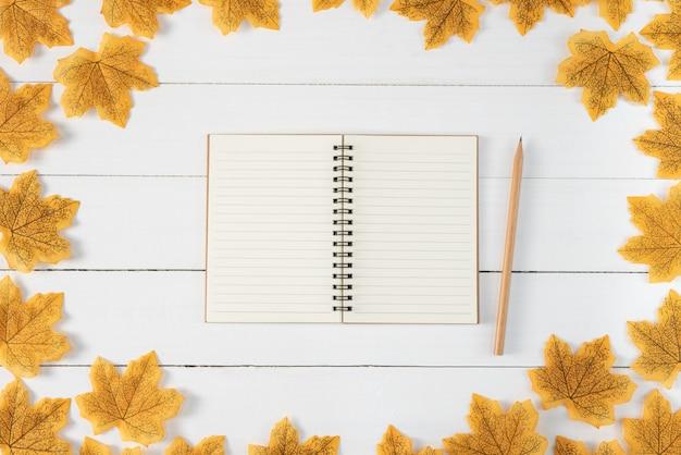 Żółci liście klonowi, książka i ołówek na białym drewnianym tle. jesień, jesień, widok z góry, miejsce.