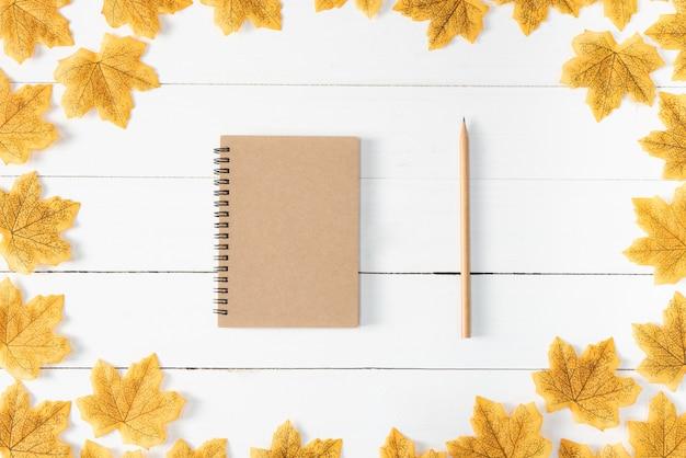 Żółci liście klonowi, książka i ołówek na białym drewnie
