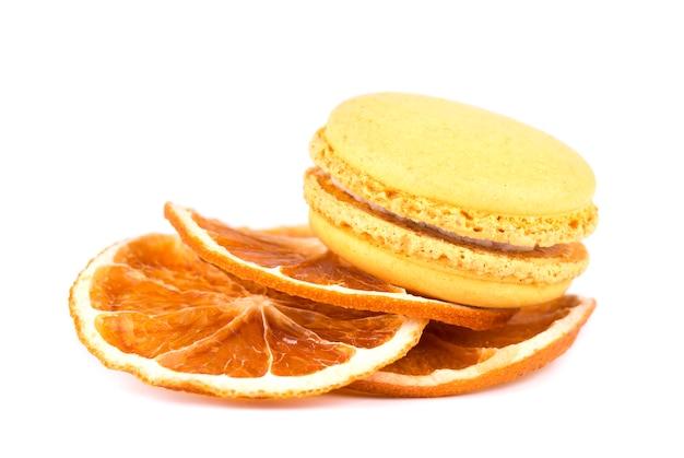 Żółci macaroons i wysuszeni pomarańczowi plasterki odizolowywający na biel przestrzeni ,.