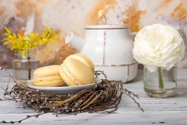 Żółci macaroons w gniazdeczku i kwiatach na białym rocznika drewnie