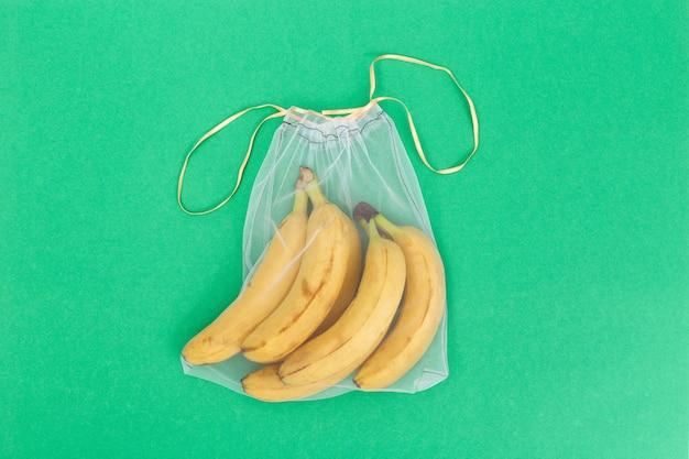 Żółci świezi banany w eco naturalnych torbach szy od siatki płótna na zielonym tle z kopii przestrzenią