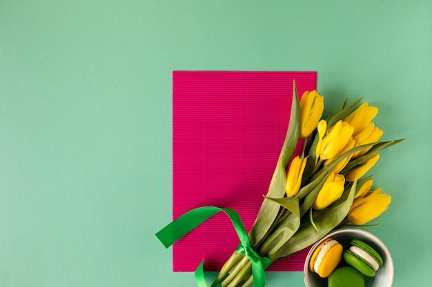 Żółci tulipany dalej i macaroons na żółtym tle