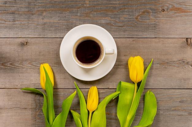 Żółci tulipany i filiżanka kawy na nieociosanym drewnianym stole. widok z góry z miejsca kopiowania.