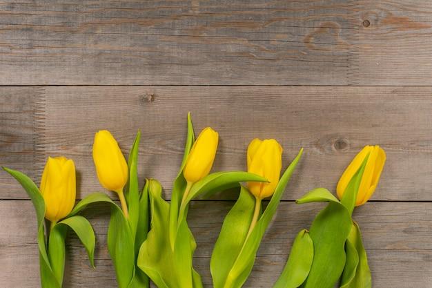Żółci tulipany na nieociosanym drewnianym stole. widok z góry z miejsca kopiowania.