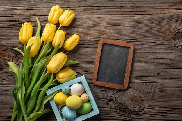 Żółci tulipany w papierowej torbie, gniazdeczko z wielkanocnymi jajkami na drewnianym tle. widok z góry z miejsca na kopię.