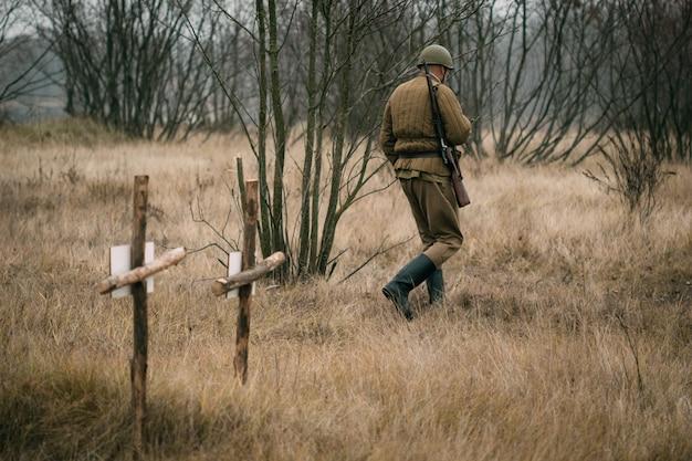 Żołnierz armii czerwonej przechodzi obok grobów