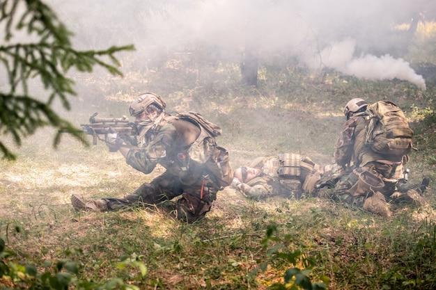 Żołnierz armii strzelający z karabinu, osłaniając kolegów na zadymionym polu bitwy