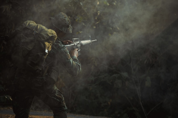 Żołnierz armii w mundurze ochronnym trzyma karabin. karabin szturmowy żołnierza sił specjalnych z tłumikiem. z dymem.