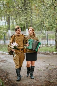 Żołnierz idzie alejką, przytulając wojskową kobietę grającą na akordeonie