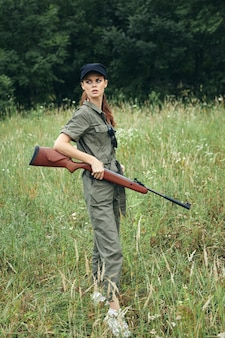 Żołnierz kobieta kobieta z bronią w dłoniach w zielonym kombinezonie spojrzeć z boku widok przycięty czarny kapelusz