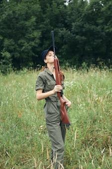 Żołnierz kobieta trzyma pistolet przed nim zielony kombinezon podróży styl życia świeże powietrze tło lasu