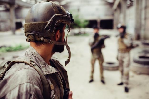 Żołnierz, który nosi mundur, patrzy na swoich przyjaciół. stoją dość daleko od niego. chłopaki odpoczywają.