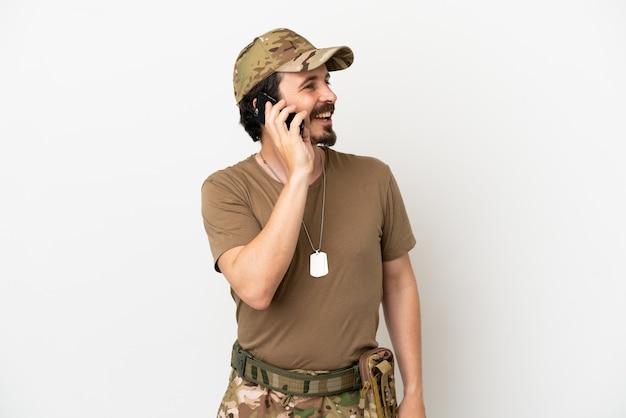 Żołnierz na białym tle na białym tle, który prowadzi rozmowę z telefonem komórkowym z kimś